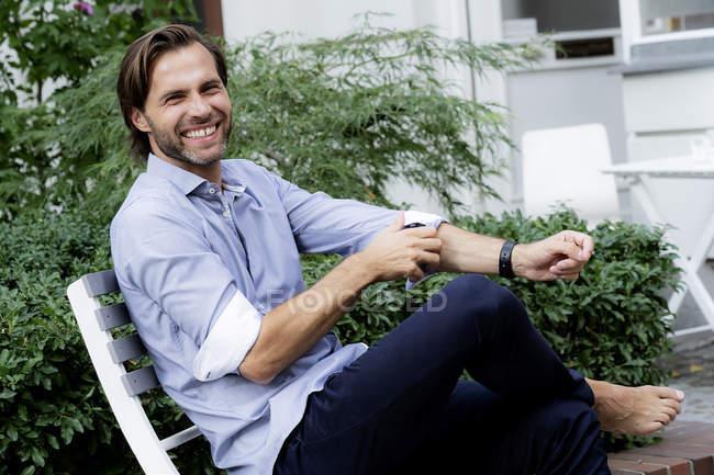 Retrato de homem feliz sentado na cadeira no jardim — Fotografia de Stock