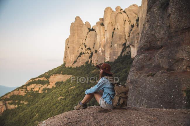 Jeune femme dans le chapeau sur le voyage de randonnée s'asseyant sur la roche — Photo de stock