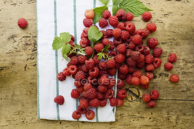 Малина, кухонний рушник і листя на дереві — стокове фото