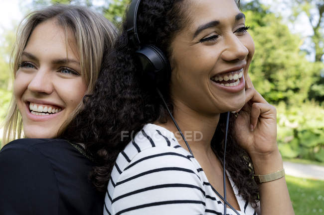 Two girlfriends in a park listening music, laughing, having fun — Stock Photo