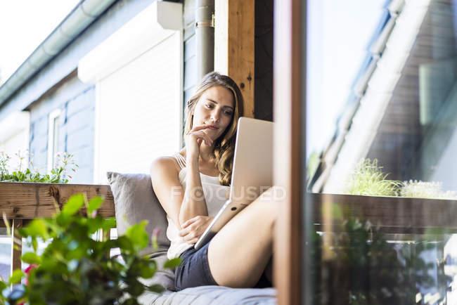 Femme souriante se détendre sur le balcon et en utilisant un ordinateur portable — Photo de stock