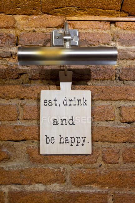 Plateau avec un dicton sur le mur de briques dans un restaurant — Photo de stock