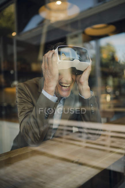 Mature businessman sitting in coffee shop, looking through VR glasses, laughing — Stock Photo