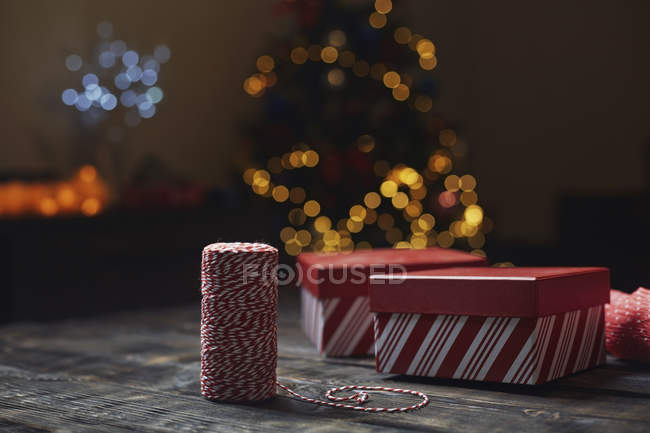 Roll of red-white packthread and gift boxes in front of lighted Christmas tree — Stock Photo