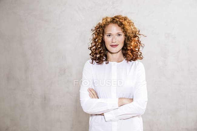 Portrait of confident redheaded young woman with arms crossed standing against grey wall — Stock Photo