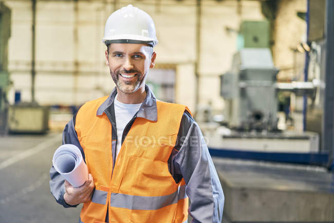 Portrait of smiling man holding blueprint in factory — Stock Photo