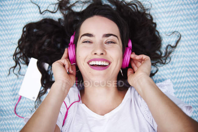 Ritratto di giovane donna felice sdraiata su una coperta ad ascoltare musica con smartphone e cuffie rosa — Foto stock