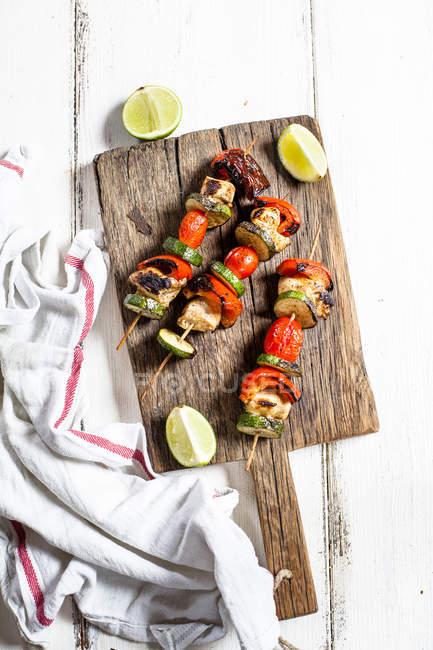 Гриль шампуры с курицей-гриль, помидорами, болгарским перцем и цуккини на разделочной доске — стоковое фото