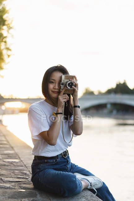 França, Paris, retrato de jovem com câmera no rio Sena ao pôr do sol — Fotografia de Stock