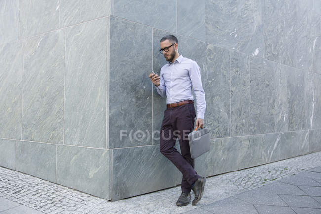 Businessman using cell phone against wall outdoors — Stock Photo