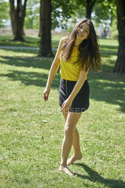 Ritratto di giovane donna felice sul prato in un parco — Foto stock