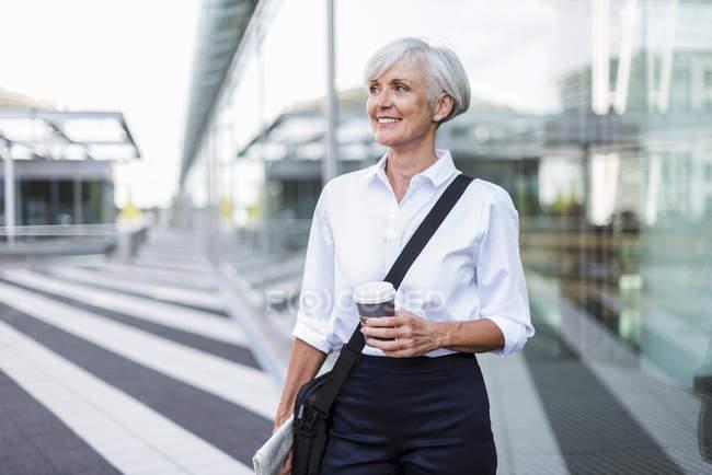 Посміхаючись старший підприємець в місті на ходу з винос кави — стокове фото