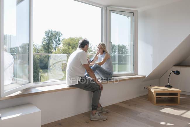 Зрелая пара с мобильным телефоном сидит у окна в пустой комнате — стоковое фото