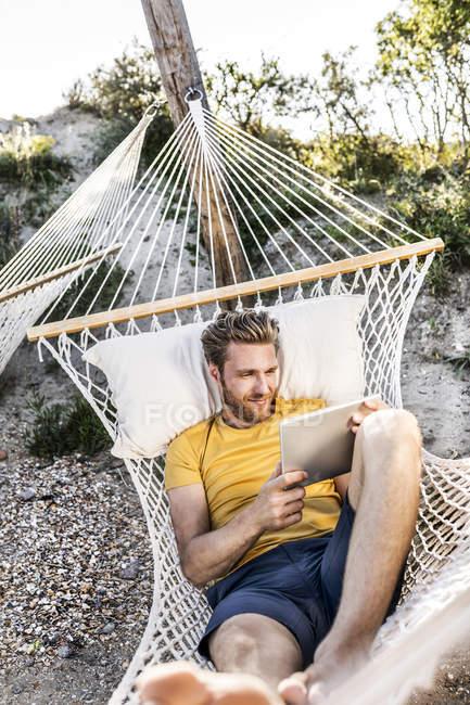 Man lying in hammock using tablet — Stock Photo