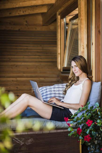 Donna rilassante sul balcone con il computer portatile — Foto stock