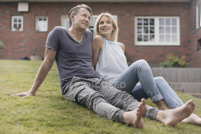 Smiling mature couple sitting in garden of house — Stock Photo