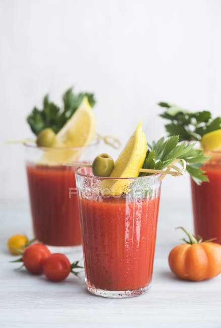 Glasses of fresh spicy tomato juice with cellery garnished with lemon slice, green olive and parsley — Stock Photo