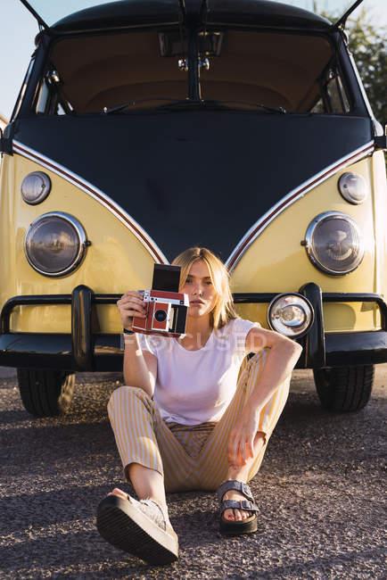 Jovem mulher segurando câmera vintage e sentado fora em uma van — Fotografia de Stock