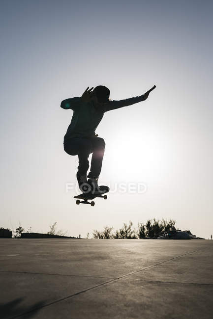 Sportive man jumping above ground with skateboard performing trick — Stock Photo