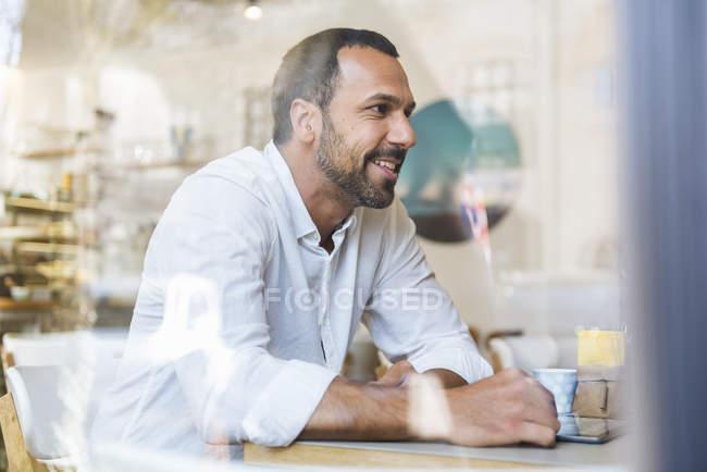 Homem sorridente com tablet em um café — Fotografia de Stock