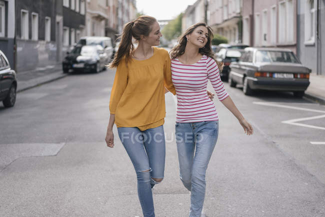 Two cheerful girlfriends having fun in city, walking arm in arm — Photo de stock