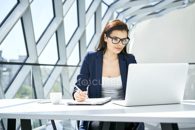 Businesswoman working at desk in modern office — Stock Photo