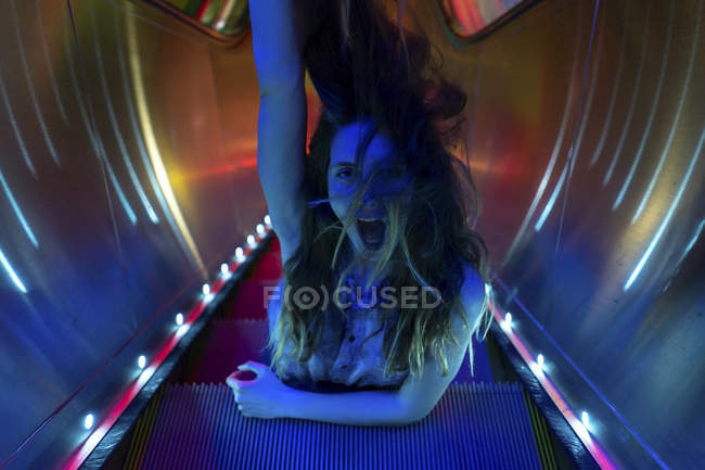 Portrait of blue illuminated screaming young woman on steps of lighted escalator — Stock Photo