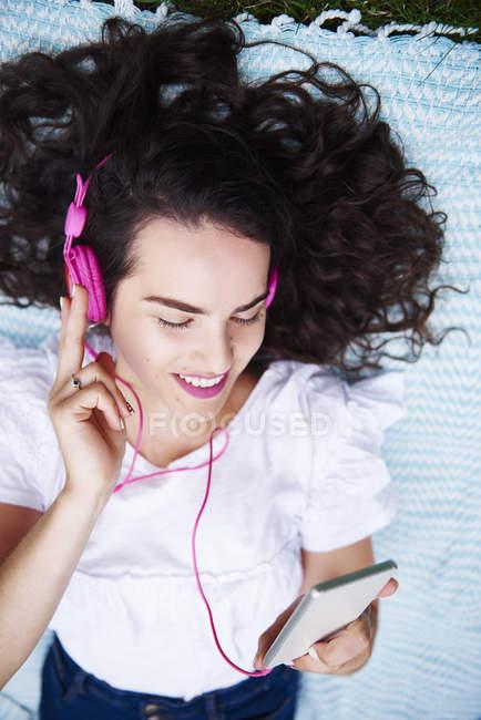 Sorrindo jovem deitado em cobertor ouvir música com smartphones e fones de ouvido rosa — Fotografia de Stock