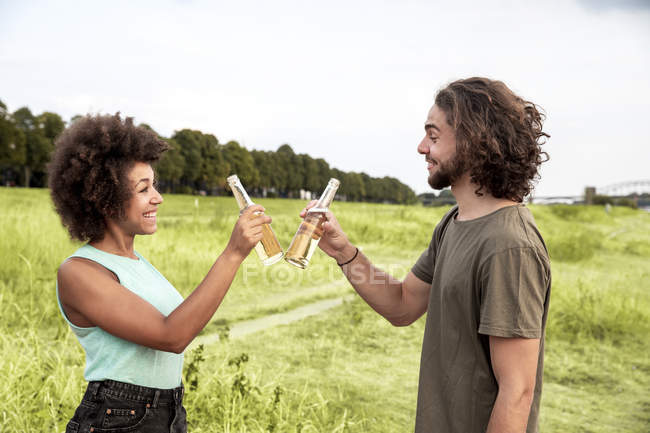 Happy couple clinking beer bottles in nature — Stock Photo