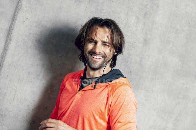 Retrato de atleta sorridente na parede de concreto — Fotografia de Stock