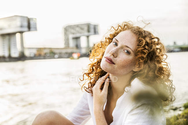 Portrait of freckled young woman with curly red hair sitting at riverside — Stock Photo