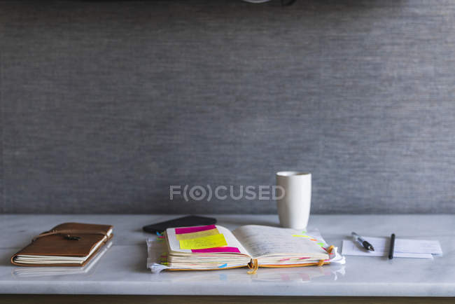 Notebooks, pen and coffee cup on shelf — Stock Photo