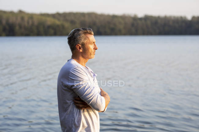 Homme pensif debout au bord du lac et regardant loin — Photo de stock
