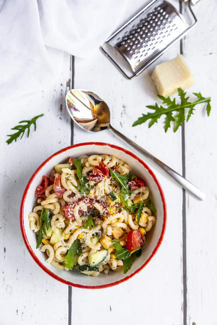 Bowl of noodle salad with corn, cucumber, tomatoes, rocket and grated parmesan — Stock Photo