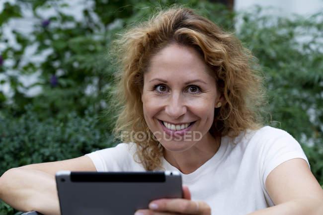 Портрет усміхнена жінка з цифровим планшетом — стокове фото