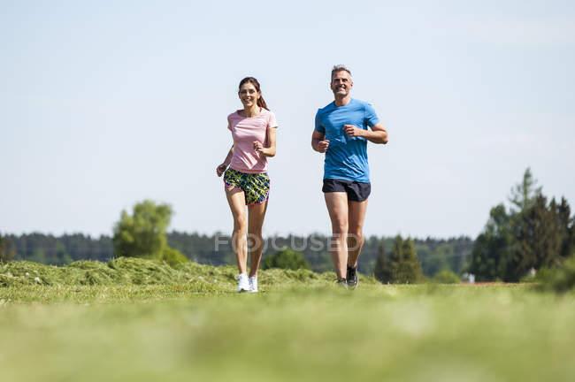 Couple running on field path — Stock Photo