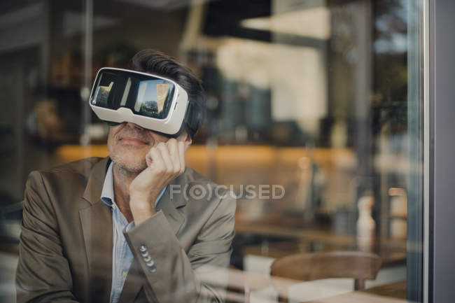 Mature businessman sitting in coffee shop, looking through VR glasses — Stock Photo