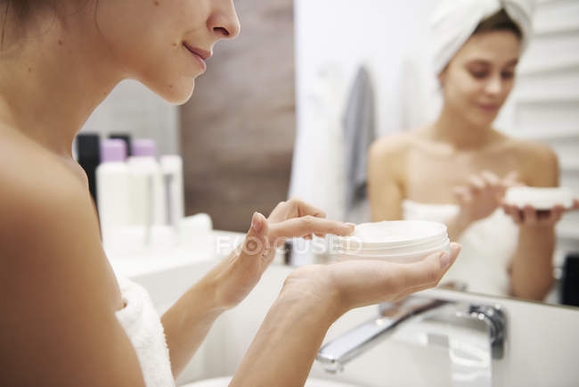 Young woman applying moisturizer in bathroom, partial view — Stock Photo