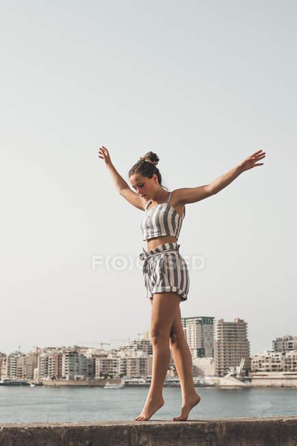 Дівчинка-підліток носить Смугасте пляж знос, балансуючи на стіні — стокове фото