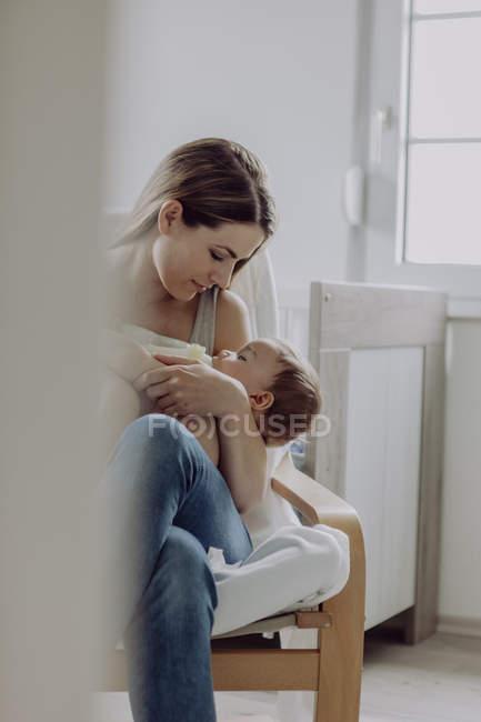 Mother feeding sleepy baby son at home — Stock Photo