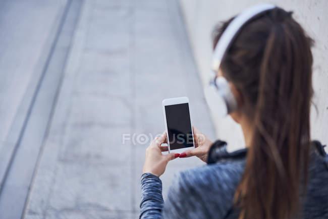 Женщина с наушниками с помощью смартфона — стоковое фото