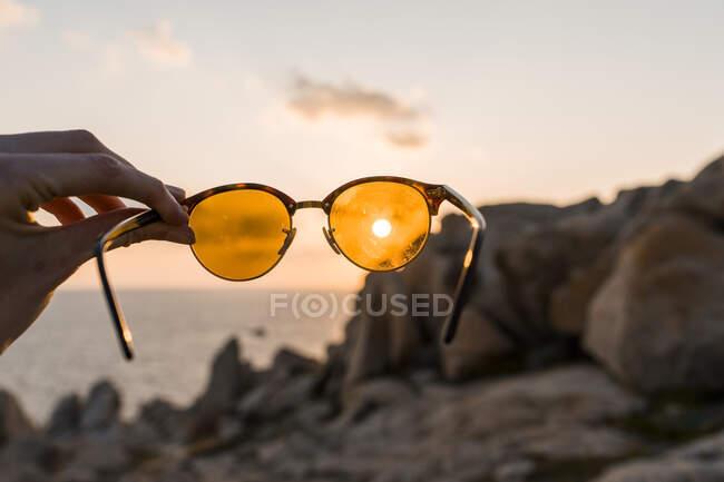 Occhiali da sole da uomo davanti al sole della sera, primo piano — Foto stock