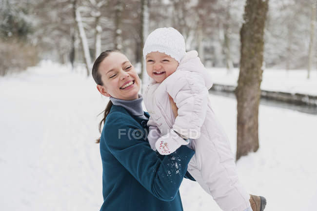 Portrait of happy baby girl having fun with her mother in snow-covered landscape — Stockfoto