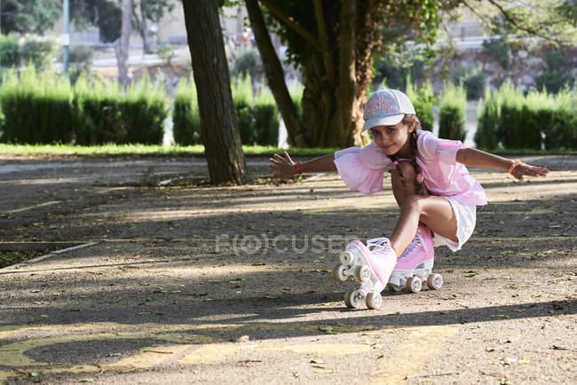Petite fille patinant et faisant des tours en stationnement — Photo de stock