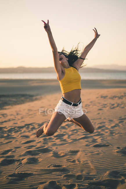 Happy teenage girl jumping in the air on beach at sunset — Stock Photo