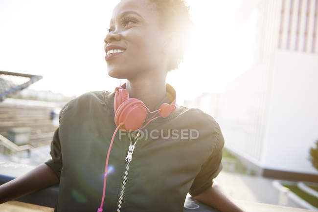 Smiling young woman with headphones at backlight — Stock Photo