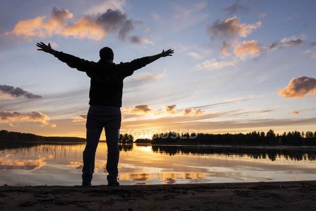 Фінляндія, Kajaani, людина спостерігає захід сонця на річці з витягнутих озброєнь — стокове фото