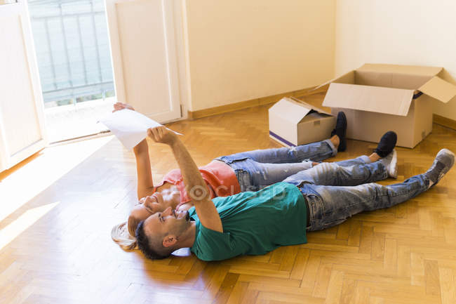 Happy couple lying side by side on the floor of new home, looking together at contract — Stock Photo