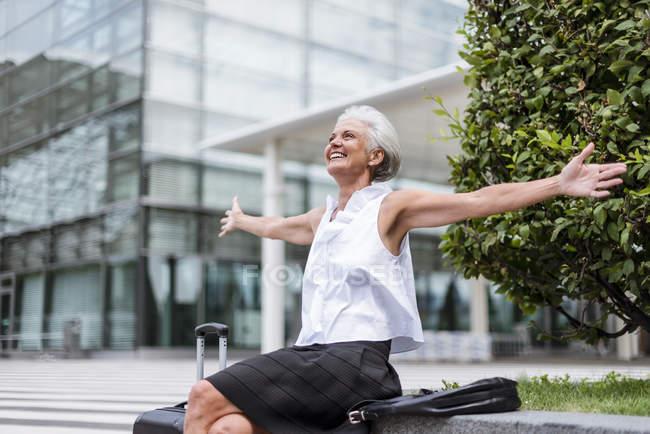 Счастливая пожилая женщина с багажом сидит в городе — стоковое фото
