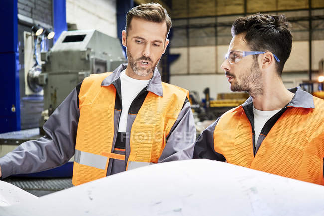 Men wearing protective workwear discussing plan in factory — Stock Photo